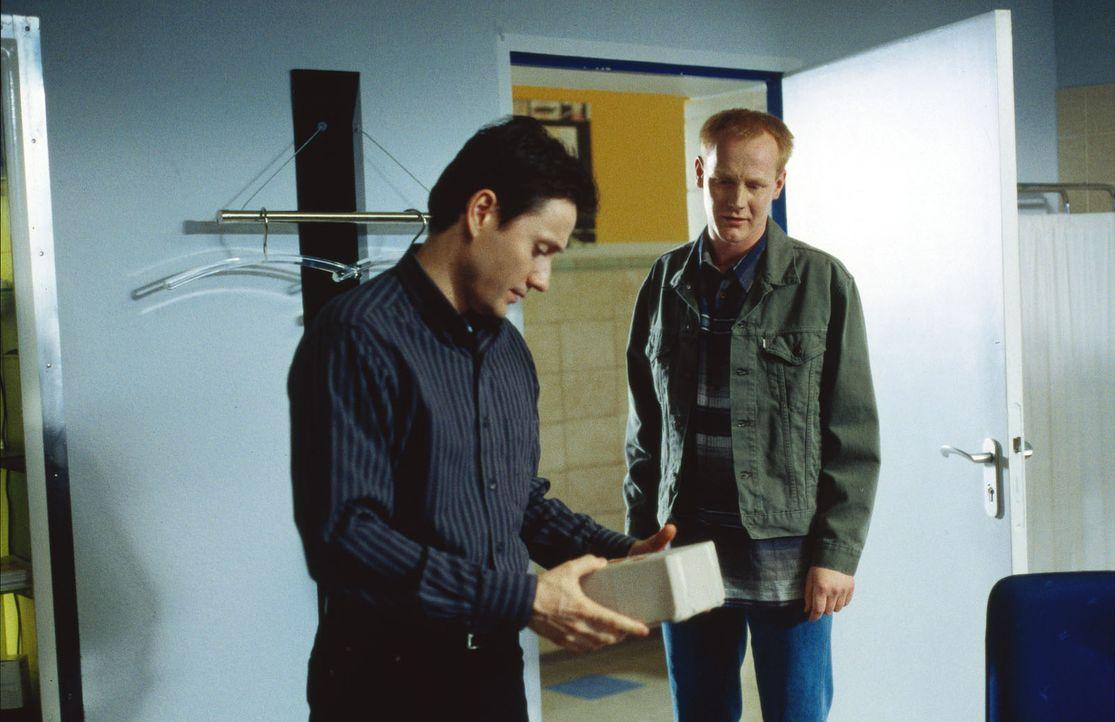 Zivi Sprosse (Sven Riemann, r.) überreicht Dr. Kampmann (Ulrich Reinthaller, l.) das Paket mit dem neuen Serum aus den USA. - Bildquelle: Daehn Sat.1