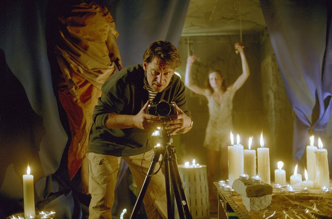 Eine Frau steht gefesselt an der Wand und Leon (Max Tidof) bereitet seine Kamera vor. Ellen soll die Letzte sein, um sein perverses Werk zu beenden. - Bildquelle: Norbert Kuhroeber Sat.1