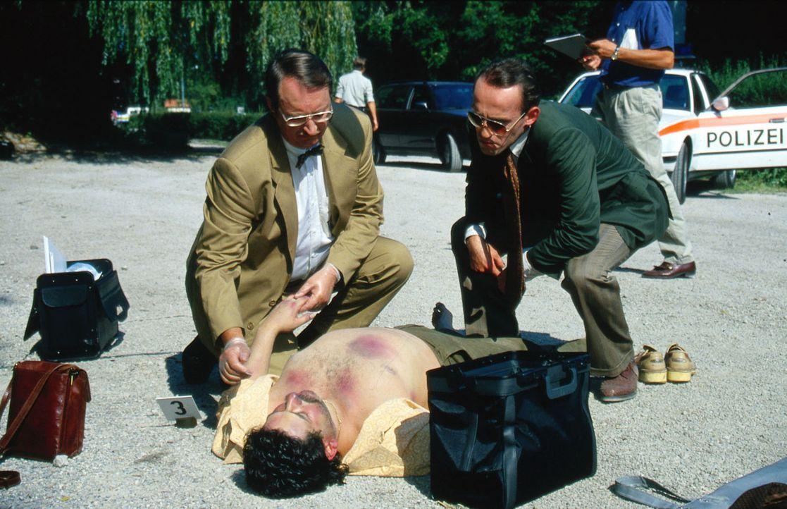 Kriminalassistent Stockinger (Karl Markovics, r.) und der Gerichtsmediziner Dr. Graf (Gerhard Zemann, l.) untersuchen die Leiche eines Mannes, der i... - Bildquelle: Ali Schafler Sat.1
