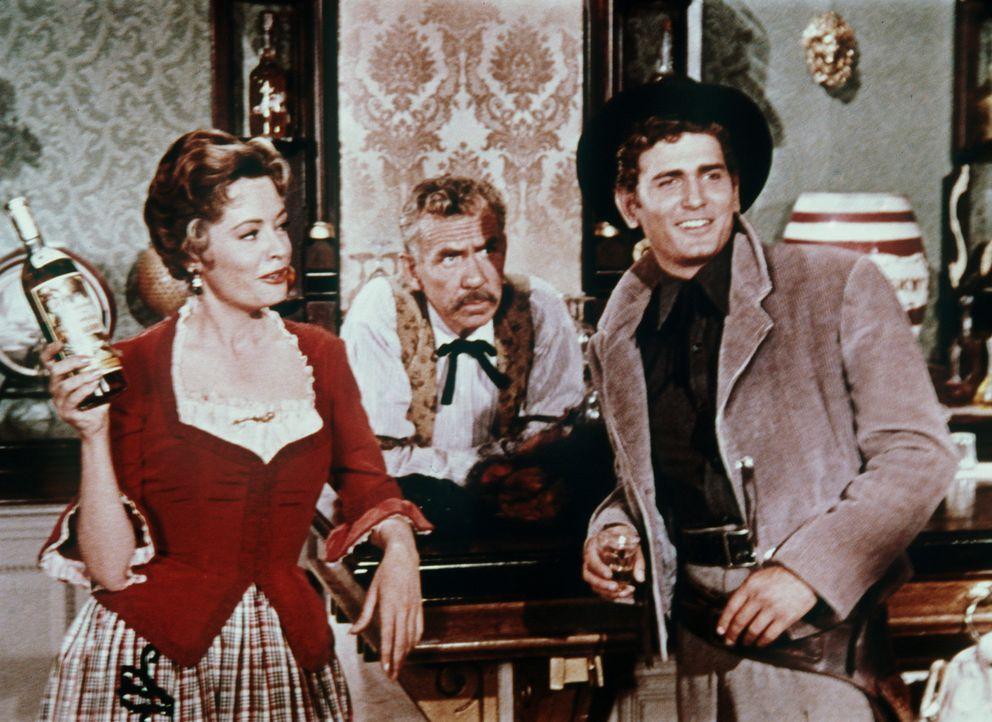 Weil Virginia City Geld braucht, versteigert Julia Bulette (Jane Greer, l.) eine Flasche Brandy, für die Little Joe (Michael Landon, r.) ein bedeute... - Bildquelle: Paramount Pictures