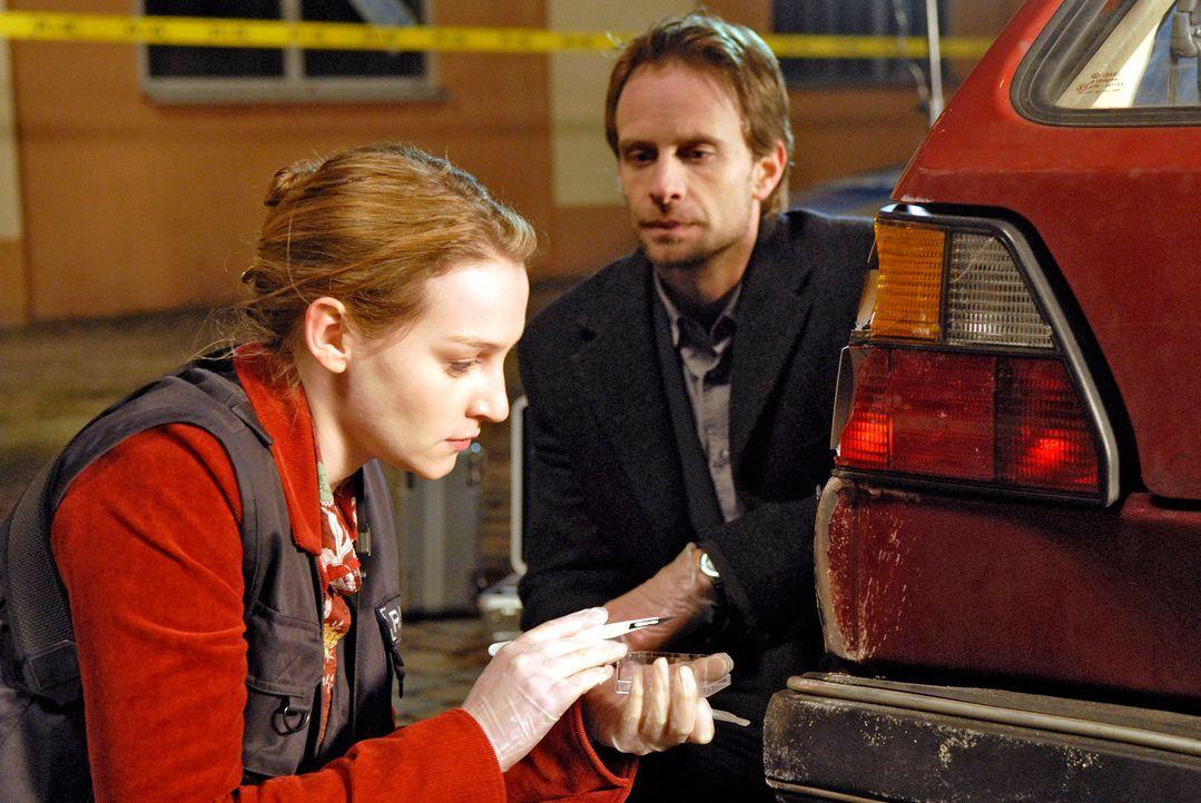 Marie (Jana Klinge, l.) sichert Lackspuren an einem in den Unfall involvierten Auto und äußert Philip (Julian Weigend, r.) gegenüber die Vermutung,... - Bildquelle: Christoph Assmann Sat.1
