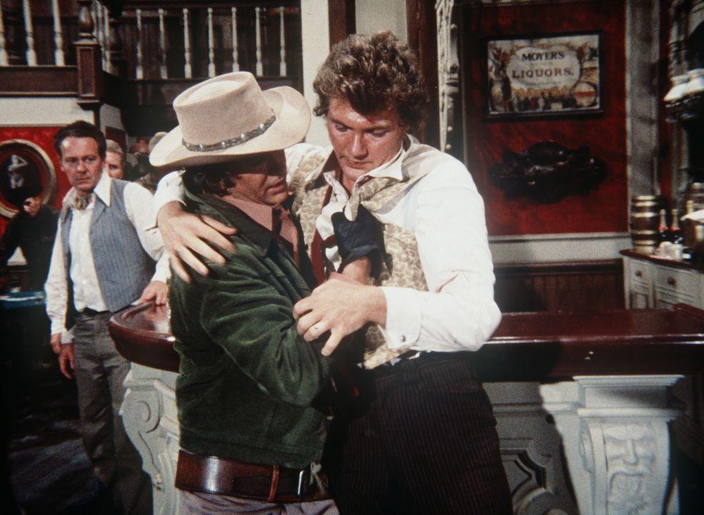 Little Joe Cartwright (Michael Landon, l.) hilft dem glücklosen Spieler Harper (Andy Robinson, r.), der im Saloon ausgenommen und verprügelt wurde. - Bildquelle: Paramount Pictures