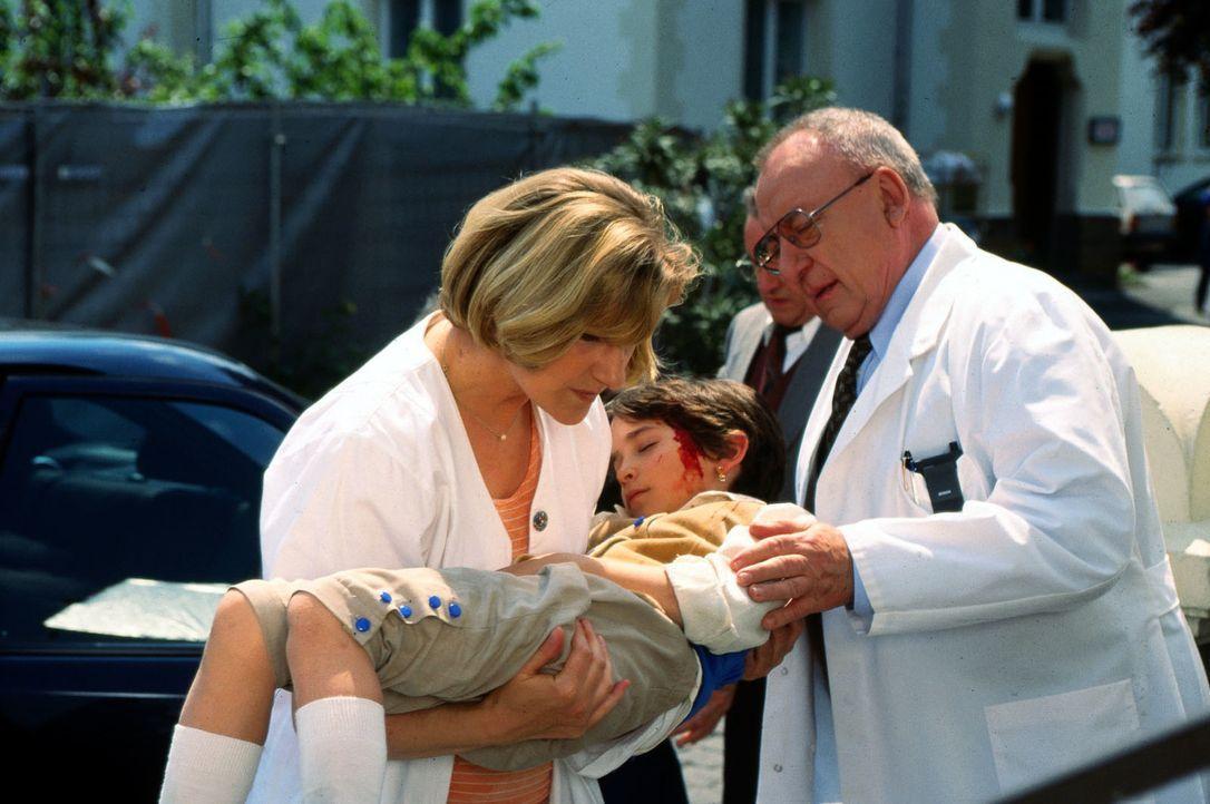 Professor Lüders (Ulrich Matschoss, r.) ist entsetzt, als er sieht, wen Schwester Hilde (Heike Jonca, l.) im Arm hat. Es ist die kleine Flora (Ana P... - Bildquelle: Andreas Stetter Sat.1
