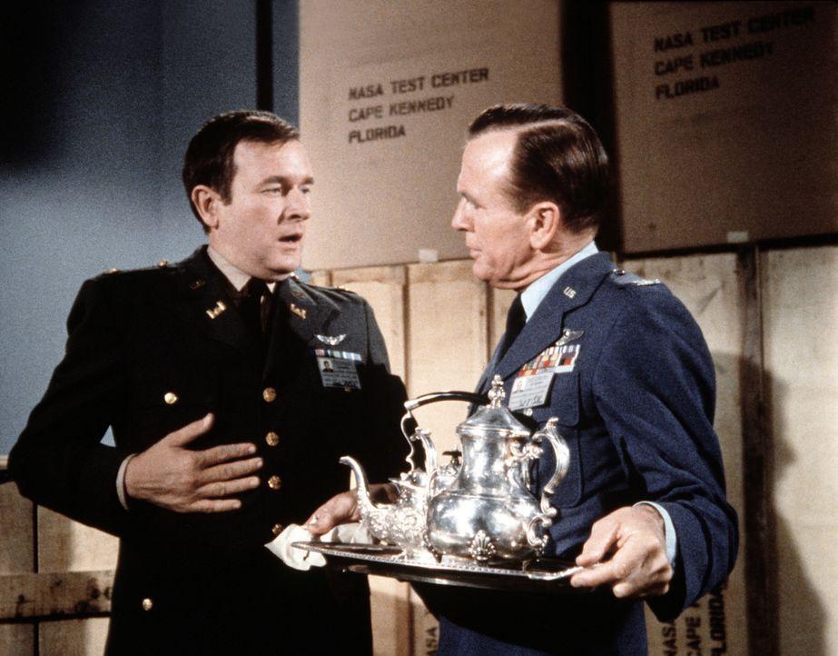 Dr. Bellows (Hayden Rorke, r.) möchte von Roger (Bill Daily, l.) wissen, wieso Tony plötzlich in Bagdad ist. - Bildquelle: Columbia Pictures