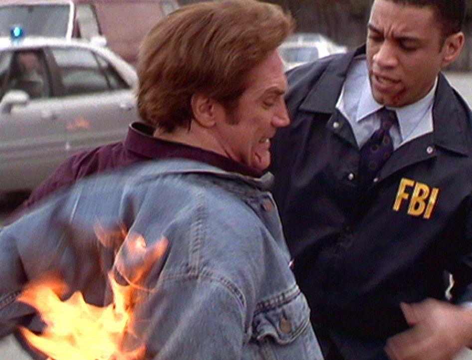 Steves (Barry Van Dyke, l.) Kleidung ist bei einem Bombenanschlag in Brand geraten. Agent Wagner (Harry J. Lennix, r.) eilt ihm zu Hilfe. - Bildquelle: Viacom