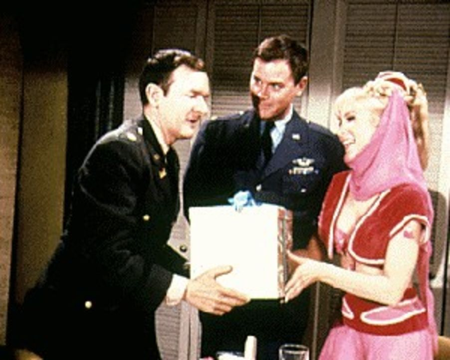 Weil Roger (Bill Daily, r.) Geburtstag hat, darf er sich ausnahmsweise auch einmal etwas von Jeannie (Barbara Eden, l.) wünschen. Unbedacht gibt er...