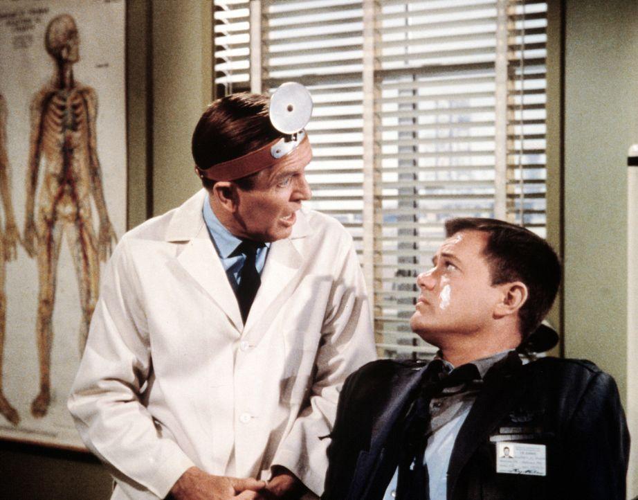 Tony (Larry Hagman, r.) zeigt mitten im Sommer plötzlich Erfrierungserscheinungen, was Dr. Bellows (Hayden Rorke, l.) doch etwas irritiert. - Bildquelle: Columbia Pictures