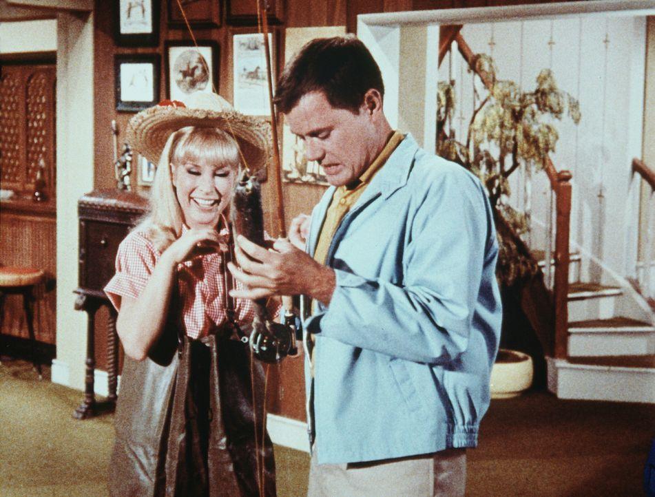Tony (Larry Hagman, r.) hat Probleme damit, dass er jetzt in seinem eigenen Wohnzimmer angeln soll. Doch Jeannie (Barbara Eden, l.) findet es herrli... - Bildquelle: Columbia Pictures