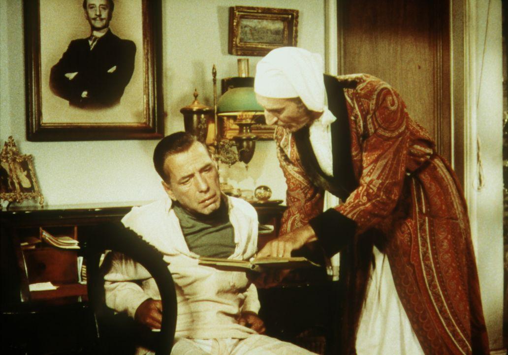 André (Basil Rathbone, r.) weist Joseph (Humphrey Bogart, l.) auf einige merkwürdige Stellen in den Geschäftsbüchern hin, was aber für den bewandert... - Bildquelle: Paramount Pictures