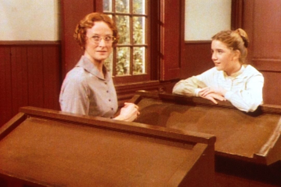 Miss Wilder (Lucy Lee Flippin, l.) hat sich zum ersten Mal verliebt. Verlegen fragt sie Laura (Melissa Gilbert, r.), wie sie Harve Miller auf sich a... - Bildquelle: Worldvision