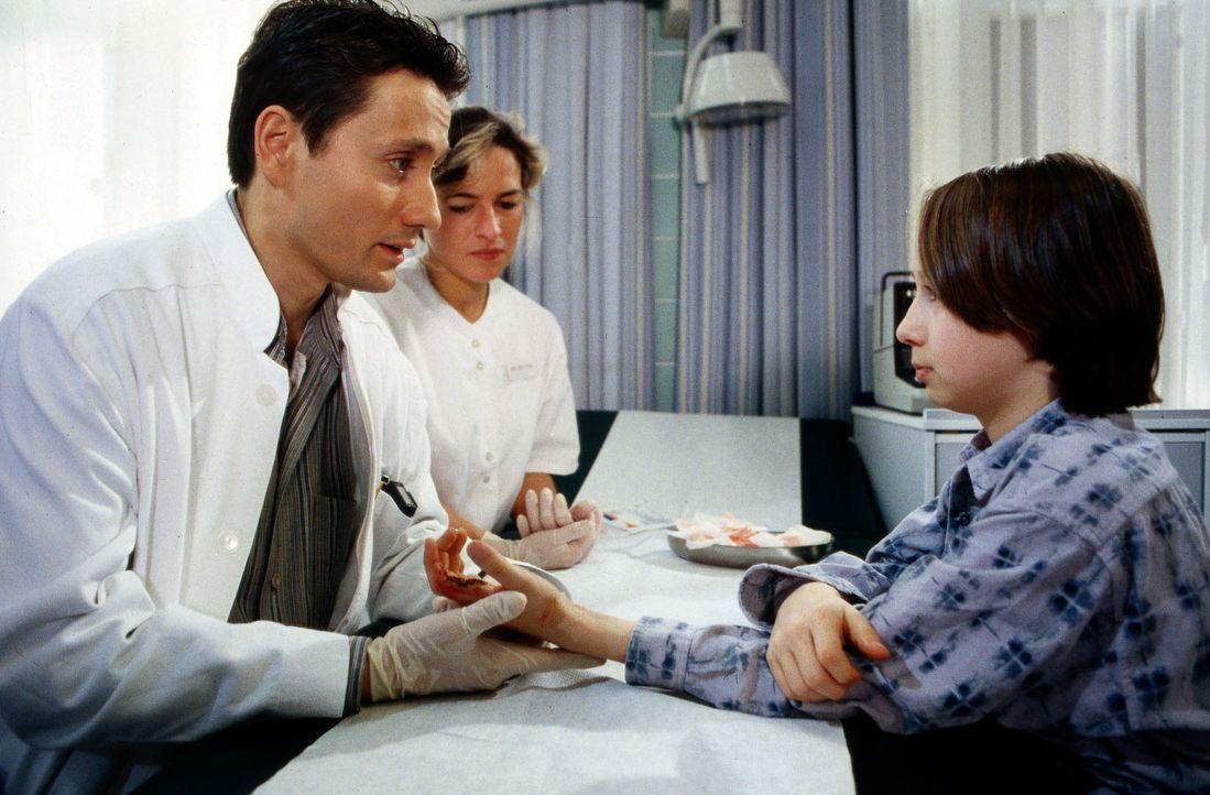 Dr. Kampmann (Ulrich Reinthaller, l.) hat die Schnittwunde des kleinen Max (Julius Jellinek, r.) versorgt. Doch irgendwie scheint ihm der Junge unge... - Bildquelle: Daehn Sat.1