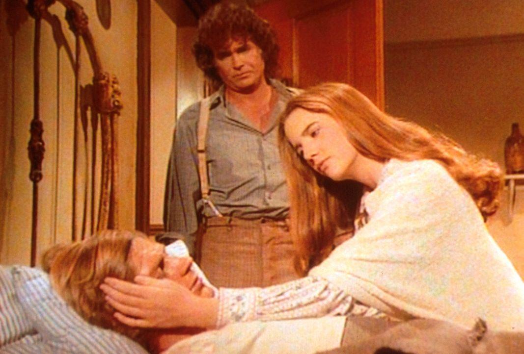 Almanzo (Dean Butler, liegend) ist an einer schweren Lungenentzündung erkrankt. Laura (Melissa Gilbert, r.) und Charles (Michael Landon, M.) sind au... - Bildquelle: Worldvision