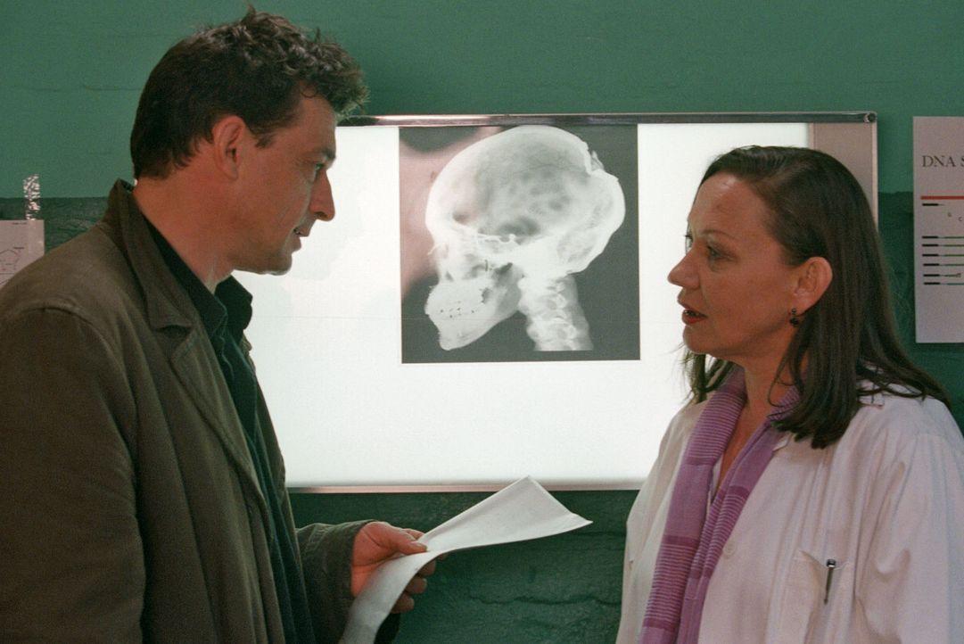 Steiner (Thomas Sarbacher, l.) erfährt von Dr. Heitmann (Karin Neuhäuser, r.), dass Beate die tödliche Kopfwunde nicht im Wald zugefügt wurde. - Bildquelle: Thomas Kost Sat.1