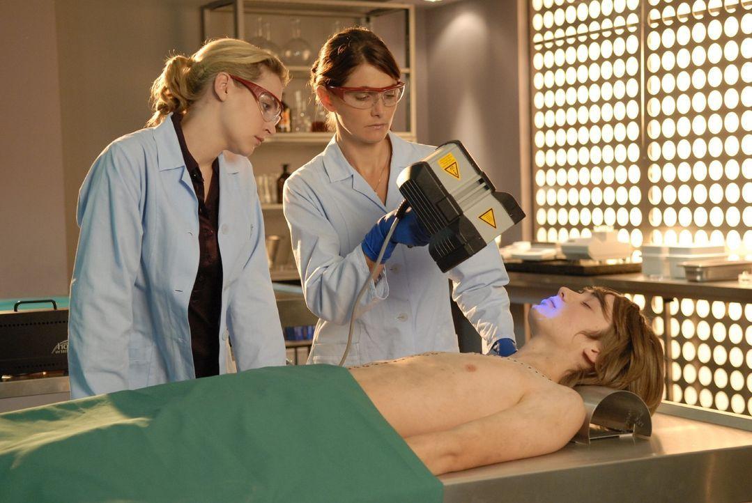 Stefanie (Nicole Maruschka, M.) bestrahlt das Gesicht des toten Florian Rosenfeld (Lorenz Wirth, r.) mit einem UV-Licht. Marie (Jana Klinge, l.) ent... - Bildquelle: Christoph Assmann Sat.1