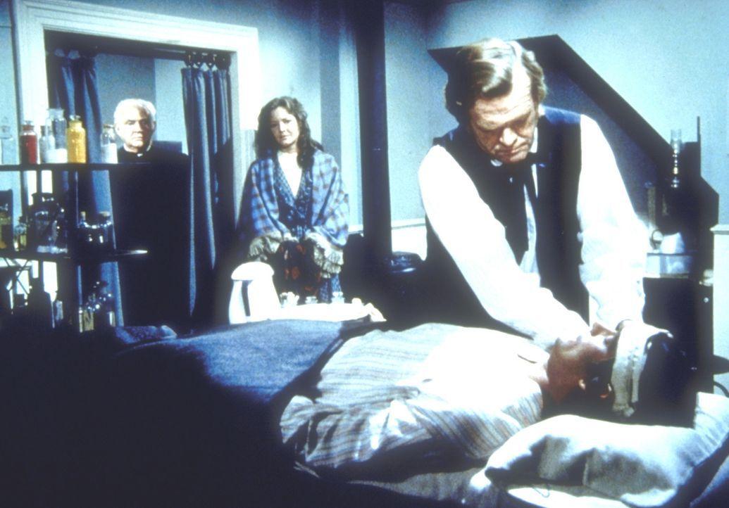 Dr. Baker (Kevin Hagen, r.) versorgt den verletzten John Carter (Stan Ivar, l.). Carters Frau Sarah (Pamela Roylance, M.) sieht besorgt zu. - Bildquelle: Worldvision
