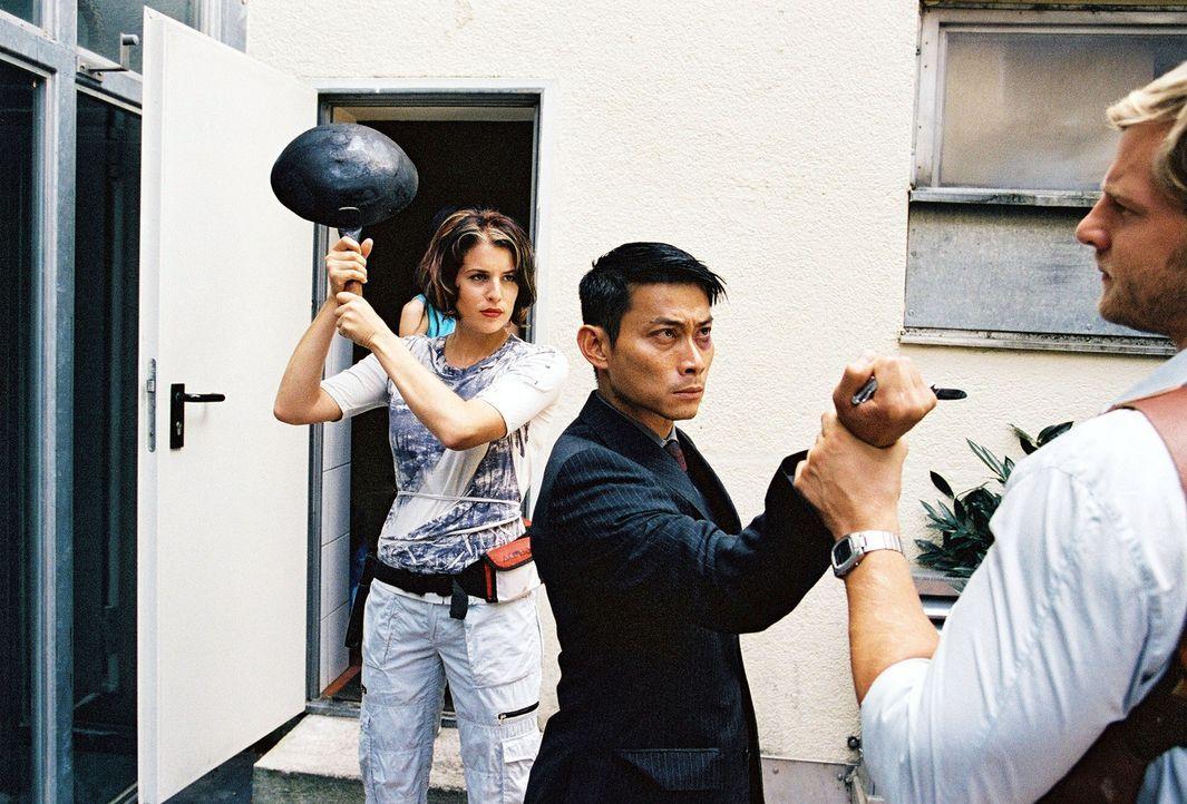 Wan Kwon (Maverick Queck, M.) bedroht Leo (Henning Baum, r.) mit einem Messer. Nina (Elena Uhlig, l.) setzt den Angreifer elegant mit einer Bratpfan... - Bildquelle: Christian A. Rieger Sat.1