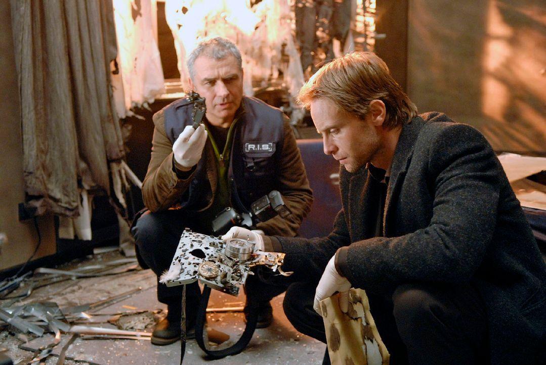 Paul (Hansa Czypionka, l.) und Philip (Julian Weigend, r.) untersuchen Stefan Bergmanns Wohnung. Sie entdecken, dass der Sprengstoff in einer Videok... - Bildquelle: Christoph Assmann Sat.1