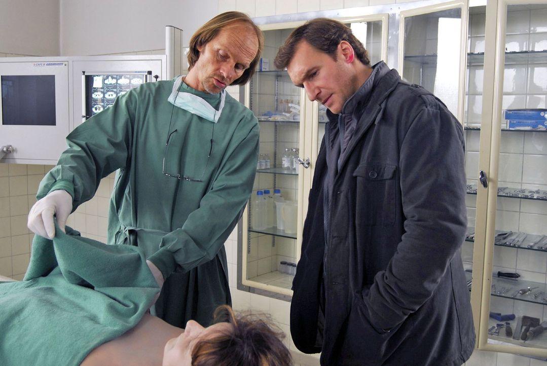Dr. Jahn (Eisi Gulp, l.) zeigt Mark (Siegfried Terpoorten, r.) die Einstichwunden an der Leiche Helga Laubers (Sabine Pürzer, vorne). - Bildquelle: Hans Seidenabel Sat.1