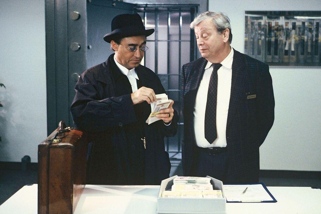 Eberhard Bronski (Nikolas Lansky, l.) holt sich aus dem Tresor seiner Bank unter der Beobachtung von Bankdirektor Schmitz (Peter Schiff, r.) zwei Mi... - Bildquelle: Alfred Raschke Sat.1