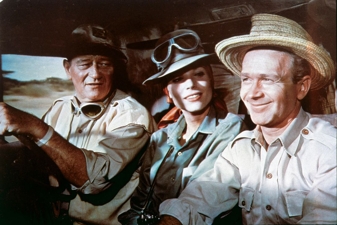 Sean Mercer (John Wayne) und Pockets (Red Buttons, r.) sind hartgesottene Großwildjäger einer Fangstation in Tansania. Eines Tages stößt die junge F... - Bildquelle: 2006 by Paramount Pictures Corporation. All Rights Reserved.
