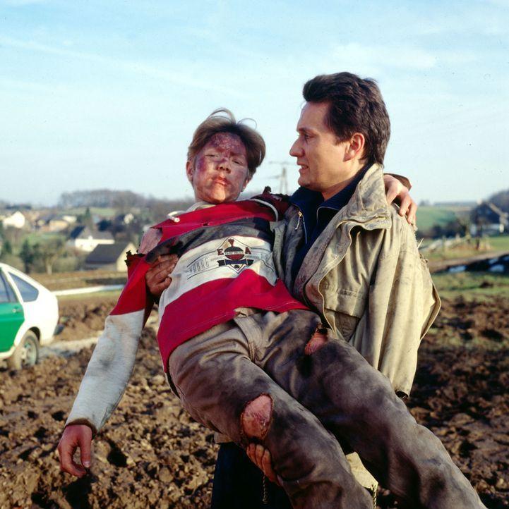 Dr. Markus Kampmann (Ulrich Reinthaller, r.) bringt den verletzten Holger (Mike Kollmar, l.) zum Notarztwagen. - Bildquelle: Janis Jatagandzidis Sat.1
