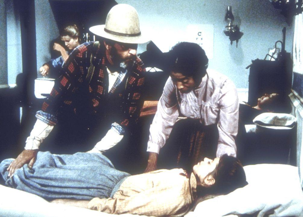 Edwards (Victor French, l.) und Hester-Sue (Ketty Lester, r.) legen die verletzte Elisabeth (Tammy Laureen, unten) in Doc Bakers Praxis aufs Bett. D... - Bildquelle: Worldvision