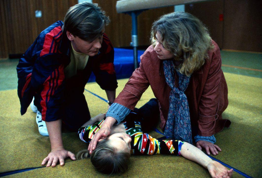 Laura Kramer (Katja Abel, M.) ist vom Schwebebalken gestürzt. Ihre Mutter Gabi (Ariane Borbach, r.) und Trainer Weiß (Frank Muth, l.) kümmern sich u... - Bildquelle: Bernd Spauke Sat.1