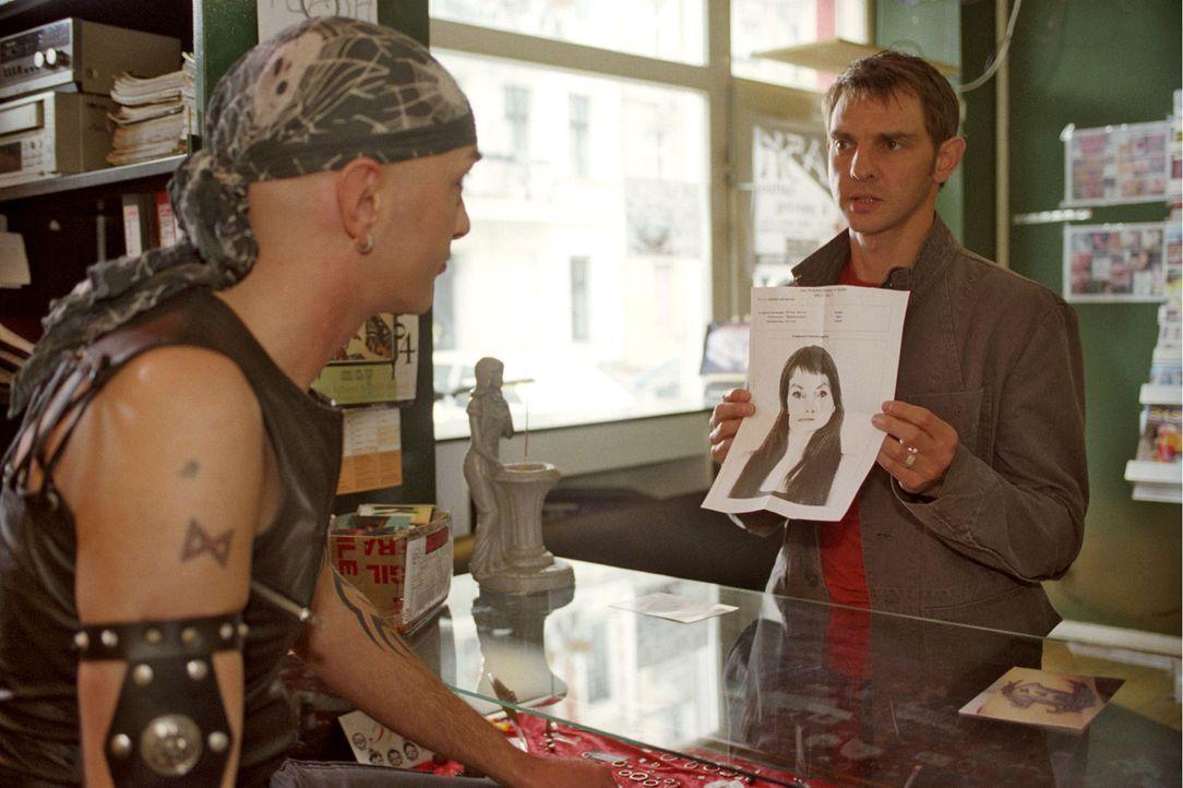 Tom (Steven Merting, r.) recherchiert in einem Tattoo-Shop und möchte von dem Ladenbesitzer (Aron Wagner, l.) wissen, ob er Veronika, die Frau auf d... - Bildquelle: Claudius Pflug Sat.1
