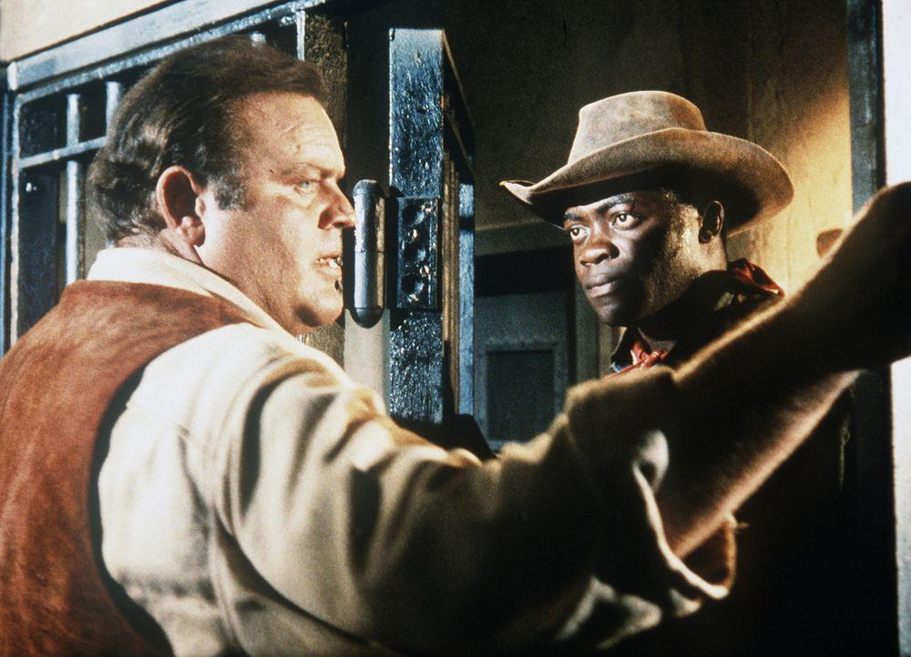 Der Schwarze Child (Yaphet Kotto, r.) befreit Hoss Cartwright (Dan Blocker, l.) aus dem Gefängnis, um ihn vor Lynchjustiz zu bewahren. - Bildquelle: Paramount Pictures