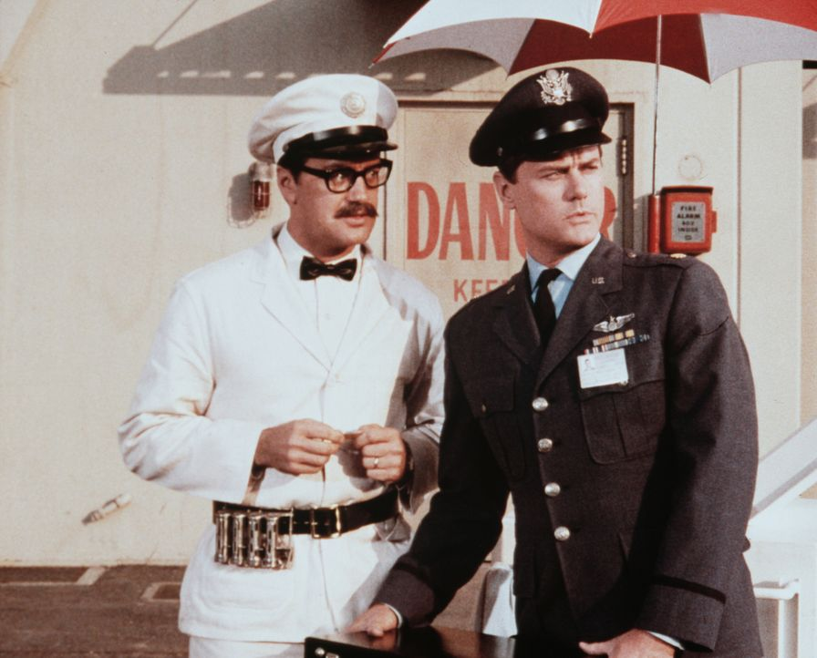 Tony (Larry Hagman, r.) und Roger (Bill Daily, l.) schaffen den Safe, in dem Jeannie gefangen ist, heimlich vom NASA-Galände. Ein Eis-Karren leistet... - Bildquelle: Columbia Pictures