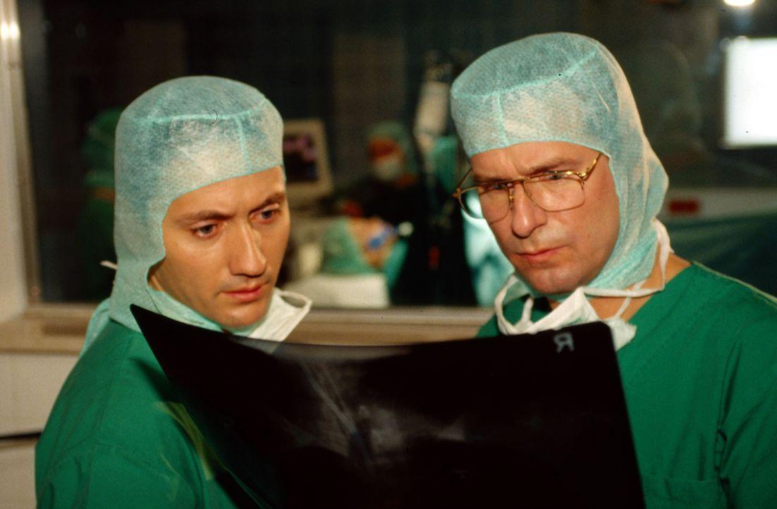 Dr. Kampmann (Ulrich Reinthaller, l.) und Dr. Lüders (Ralf Lindermann, r.) begutachten die Röntgenaufnahme von Denny. - Bildquelle: Norbert Kuhroeber Sat.1