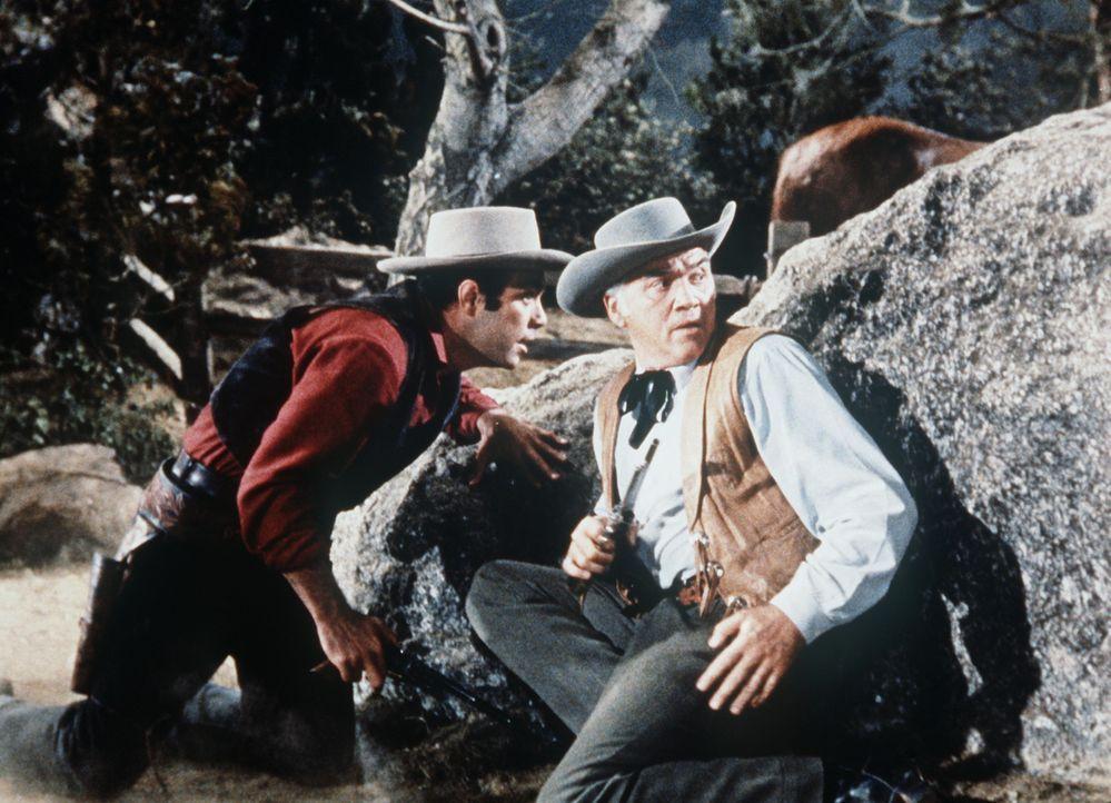 Ben Cartwright (Lorne Greene, r.) und sein Sohn Adam (Pernell Roberts) geraten in ein Feuergefecht mit dem Gauner Burdette. - Bildquelle: Paramount Pictures