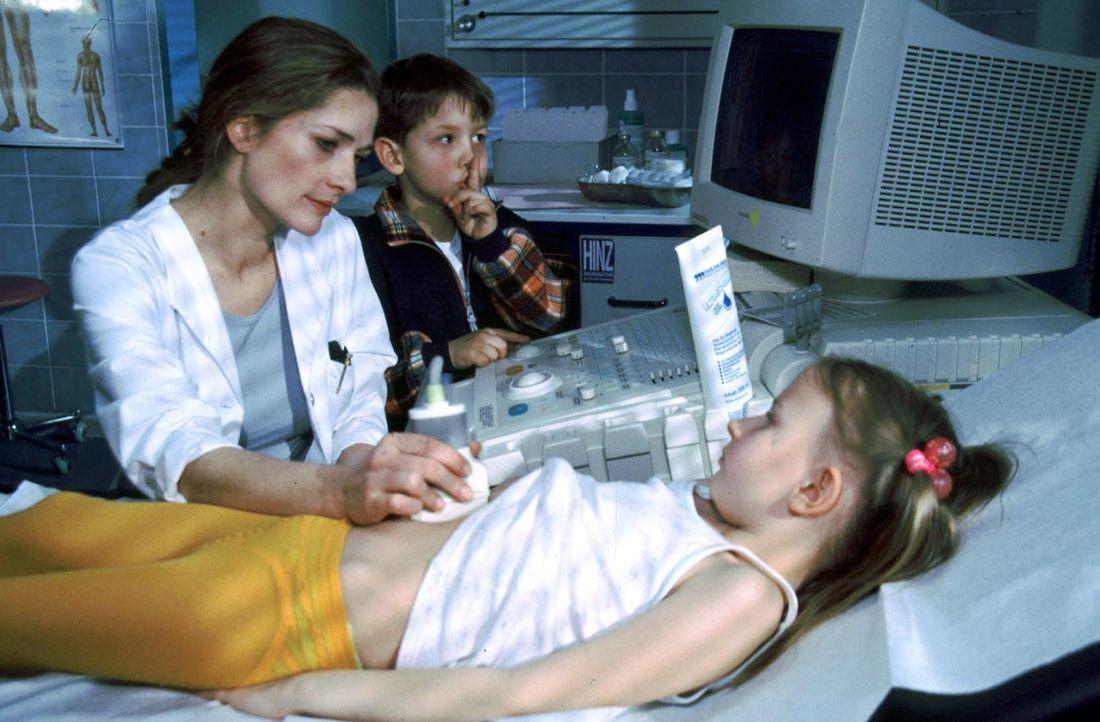 Dr. Johanna Kaminski (Iris Böhm, l.) untersucht die kleine Inka (Romina Mosch, liegend) mit Ultraschall. Tobi (Konstantin Efremides, M.) hat seine F... - Bildquelle: Christina Kurby Sat.1