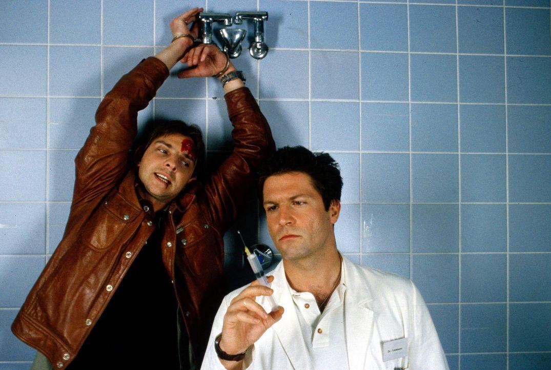 Tom Borkmann (Steven Merting, l.) vom Drogendezernat gerät in eine gefährliche Situation, als er den angesehenen Chirurgen Dr. Karsten Feldmann (Fra... - Bildquelle: Alfred Raschke Sat.1