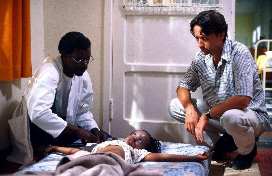 Dr. Otjumo (Tshamano Sebe, l.) zeigt Dr. Kampmann (Ulrich Reinthaller, r.) die schwerkranke Samila (Hanneke Koopmans, M.). Wenn das Mädchen nicht sc... - Bildquelle: Norbert Kuhroeber Sat.1