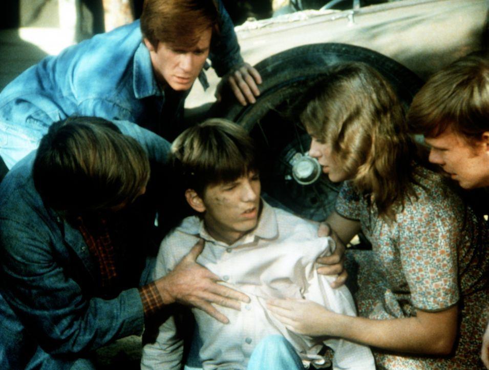Bei einer Reparatur ist ein Wagen auf Jim-Bob (David W. Harper, M.) gefallen. Er wird von seinem Vater John (Ralph Waite, l.) und seinen Geschwister... - Bildquelle: WARNER BROS. INTERNATIONAL TELEVISION