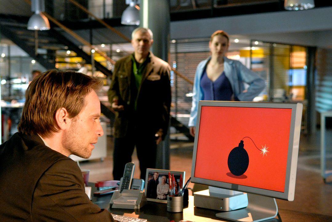 Als Philip (Julian Weigend, l.) sein Büro betritt, bemerkt er, dass sein Rechner schon angeschaltet ist. Auf dem Monitor blinkt das Symbol einer Bom... - Bildquelle: Christoph Assmann Sat.1