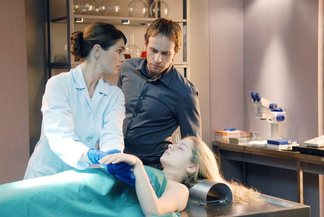 Dr. Stefanie Peters (Nicole Marischka, l.) zeigt Philip (Julian Weigend, r.) die Verletzungen an der Leiche Svenja Wetzels (Shalyn Casar, M.). - Bildquelle: Christoph Assmann Sat.1